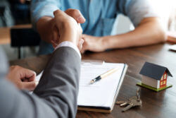 two people shaking hands over a property agreement with the help of an escrow company