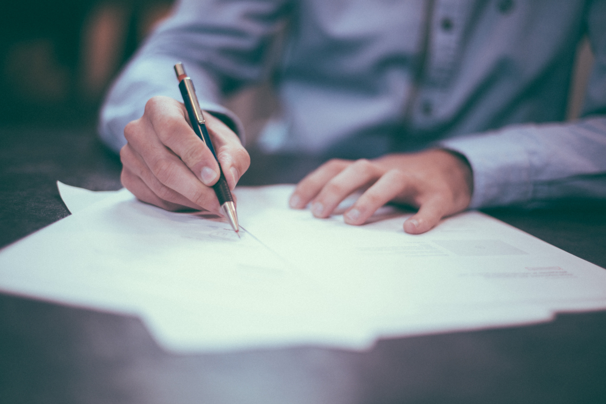 man signing trust agreements documents on a wooden desk.